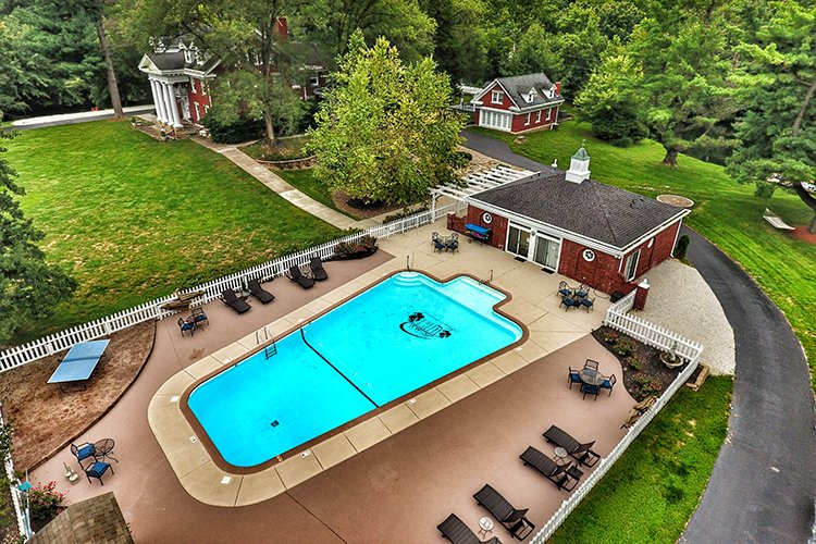 Aerial view of a swimming pool surrounded by lounge chairs with red brick mansion in background