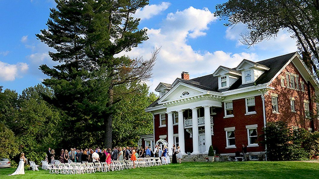 Wedding scene in front of a two-story red brick mansion with four large columns
