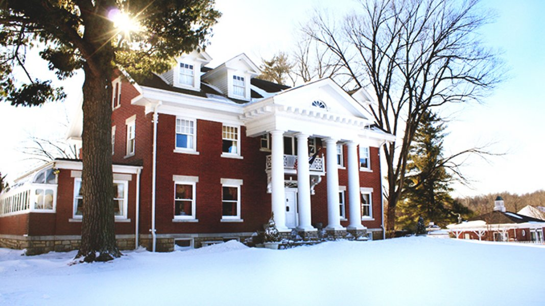 Winter scene of a red brick mansion with four white columns accenting the front porch