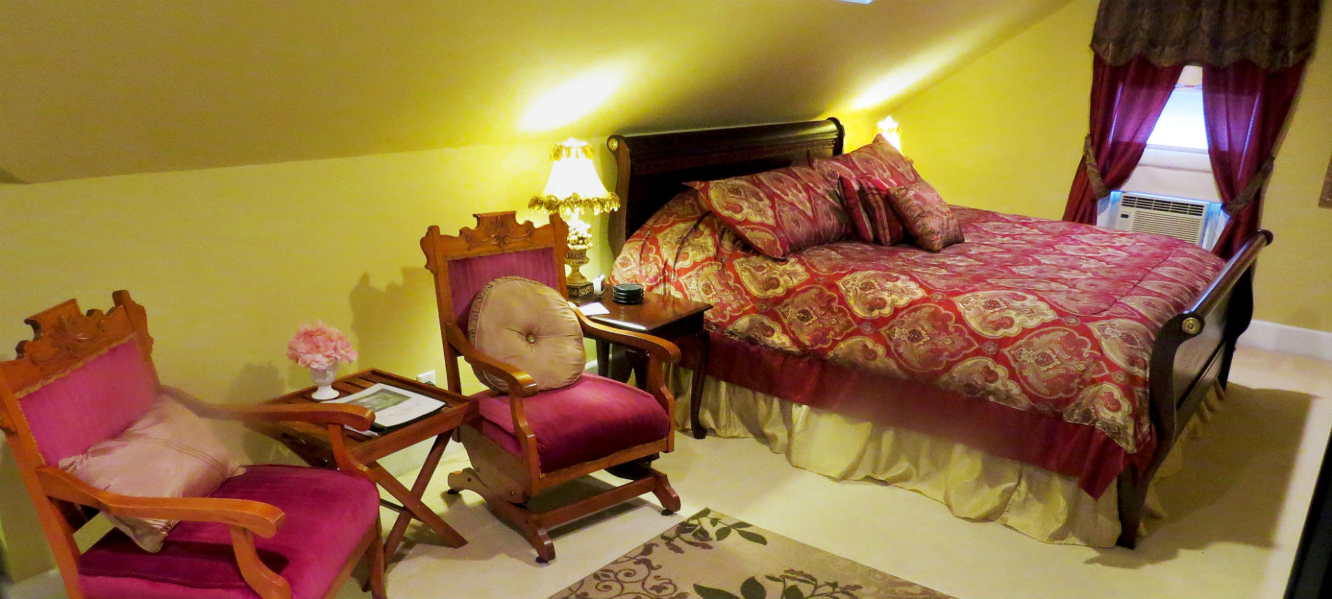 Two wood chairs with red velvet cushions next to a cherry sleigh bed with a burgundy and gold bedspread