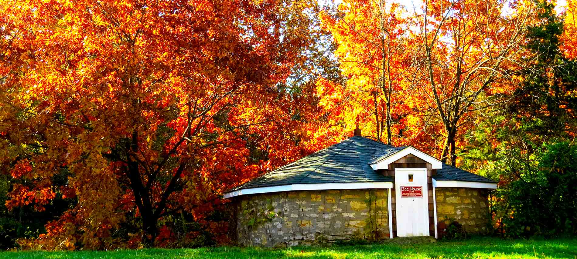 Fall leaves in their oranges and reds abound in this view of the old cyndrilical ice house.