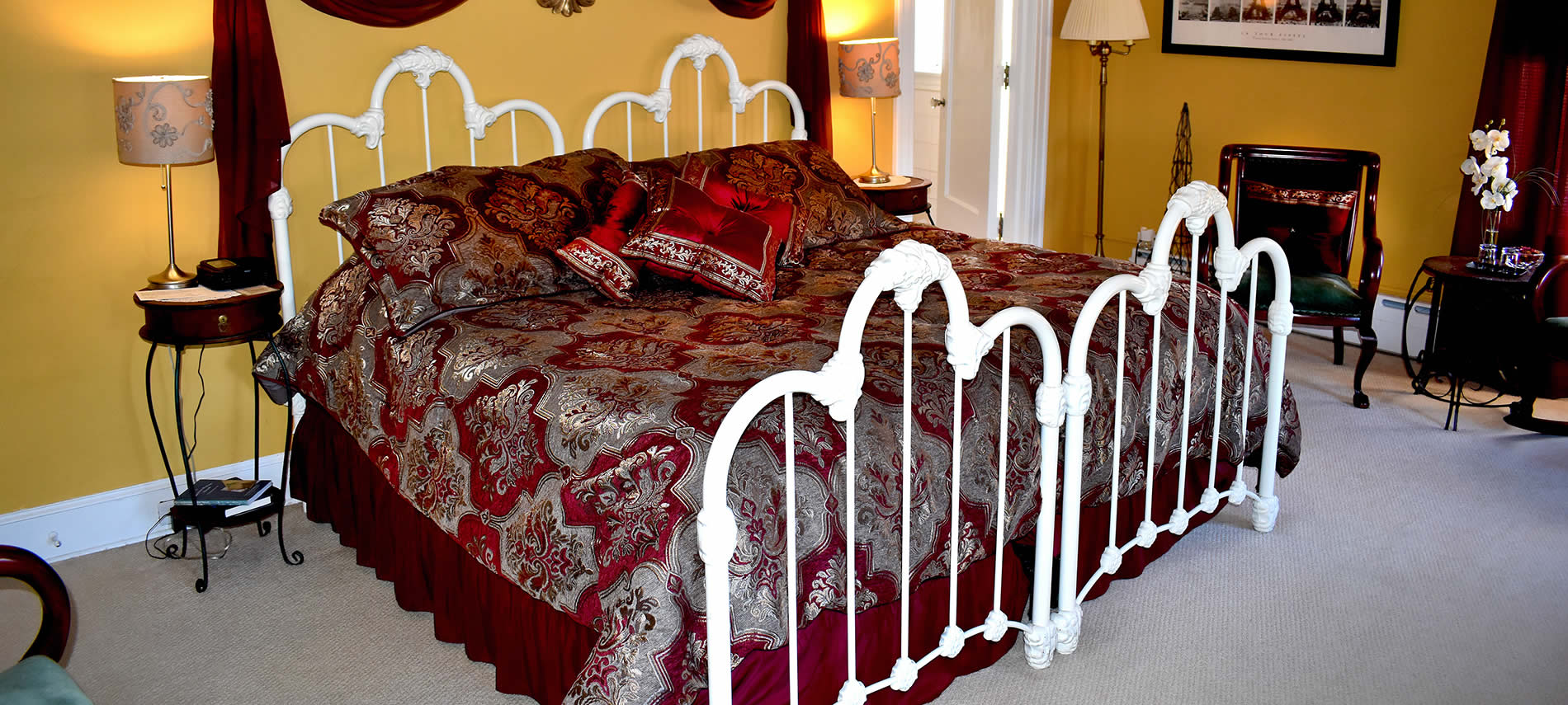 Burgundy and gold bedspread on white wrought iron bed with sitting area in background.