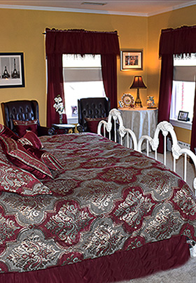 Burgandy bedspread on wraught iron bed with sitting area in background.
