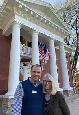 New owners Jack and Monica standing by red brick house with white pillars and flags hanging on house.