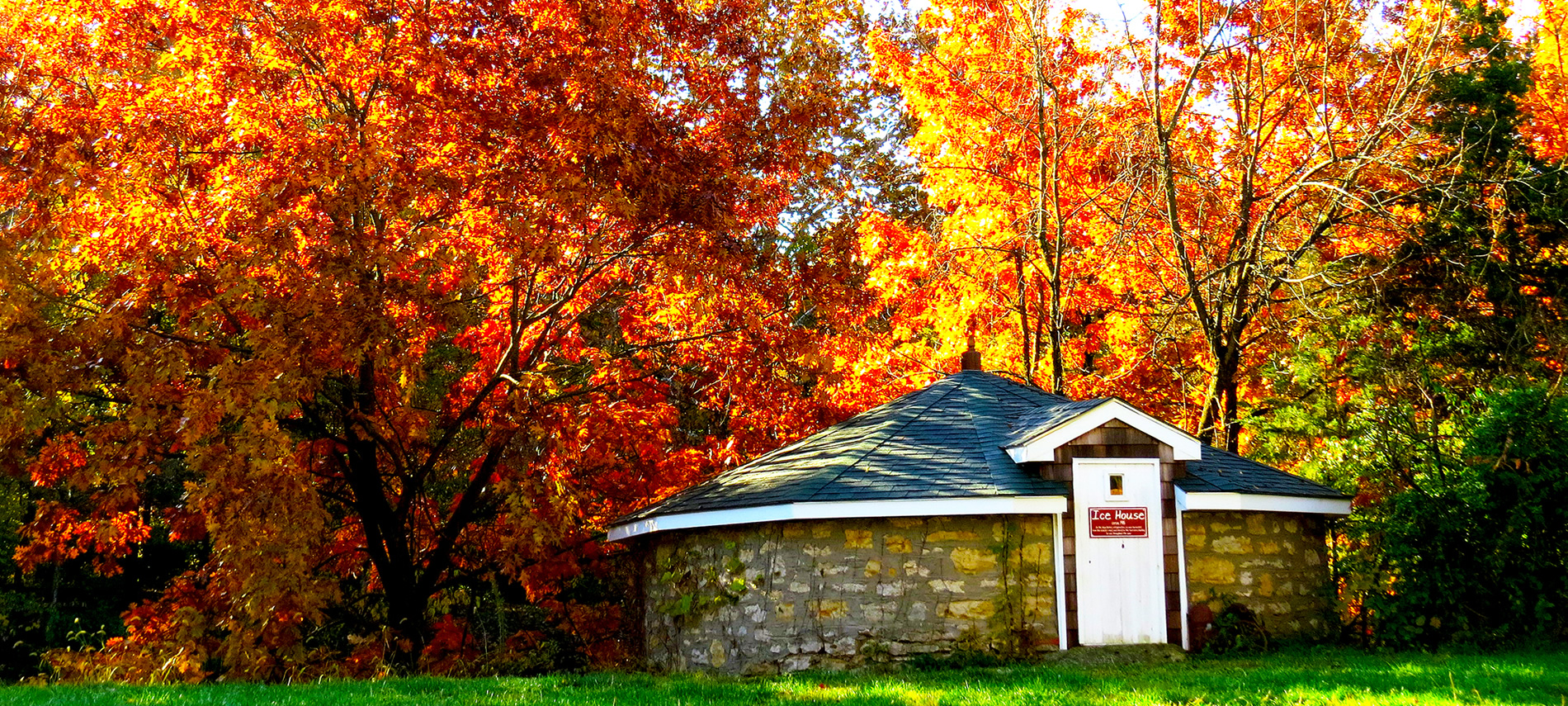 A squat brown stone building with a white door in front of trees with brilliant red and yellow leaves