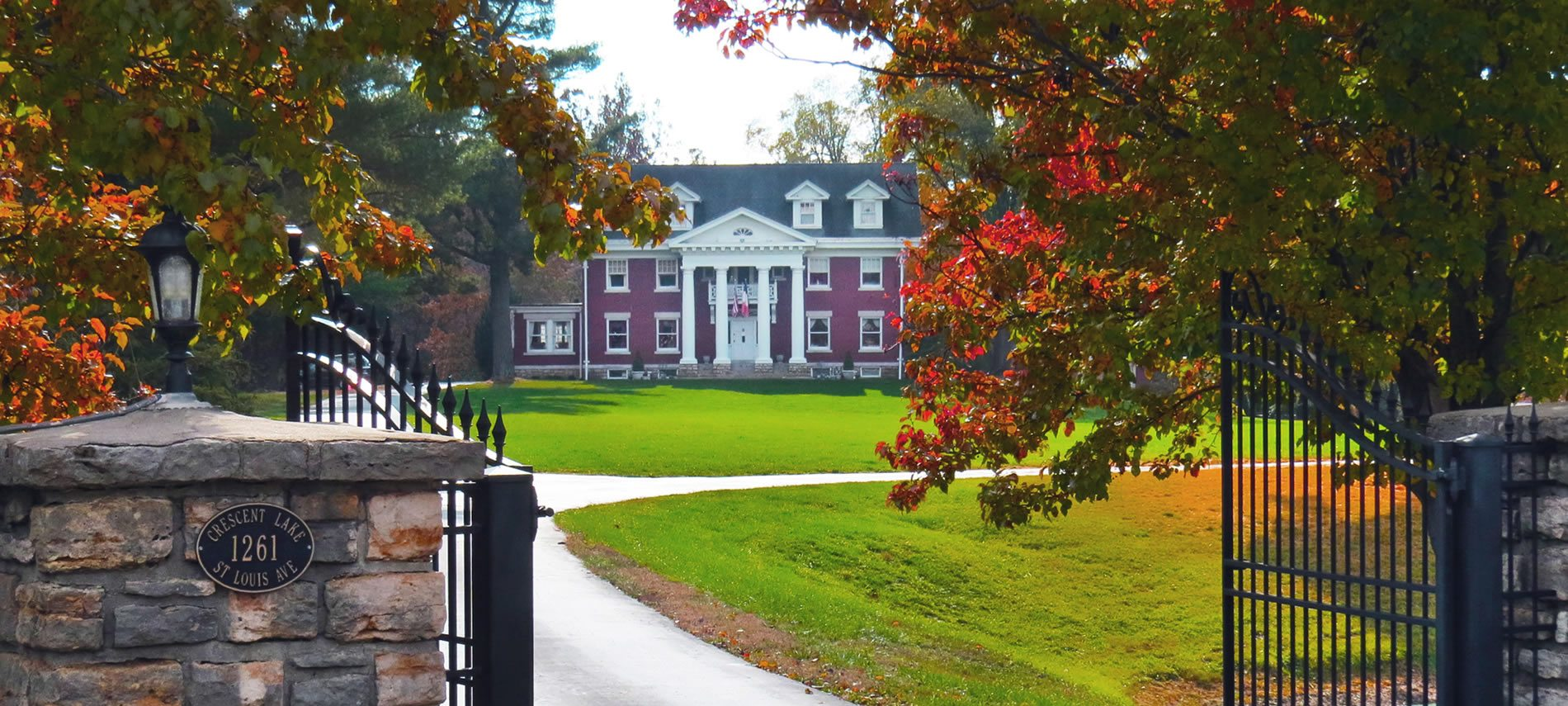 A gated entrance to a driveway with a red brick mansion with four white columns visible in the distance