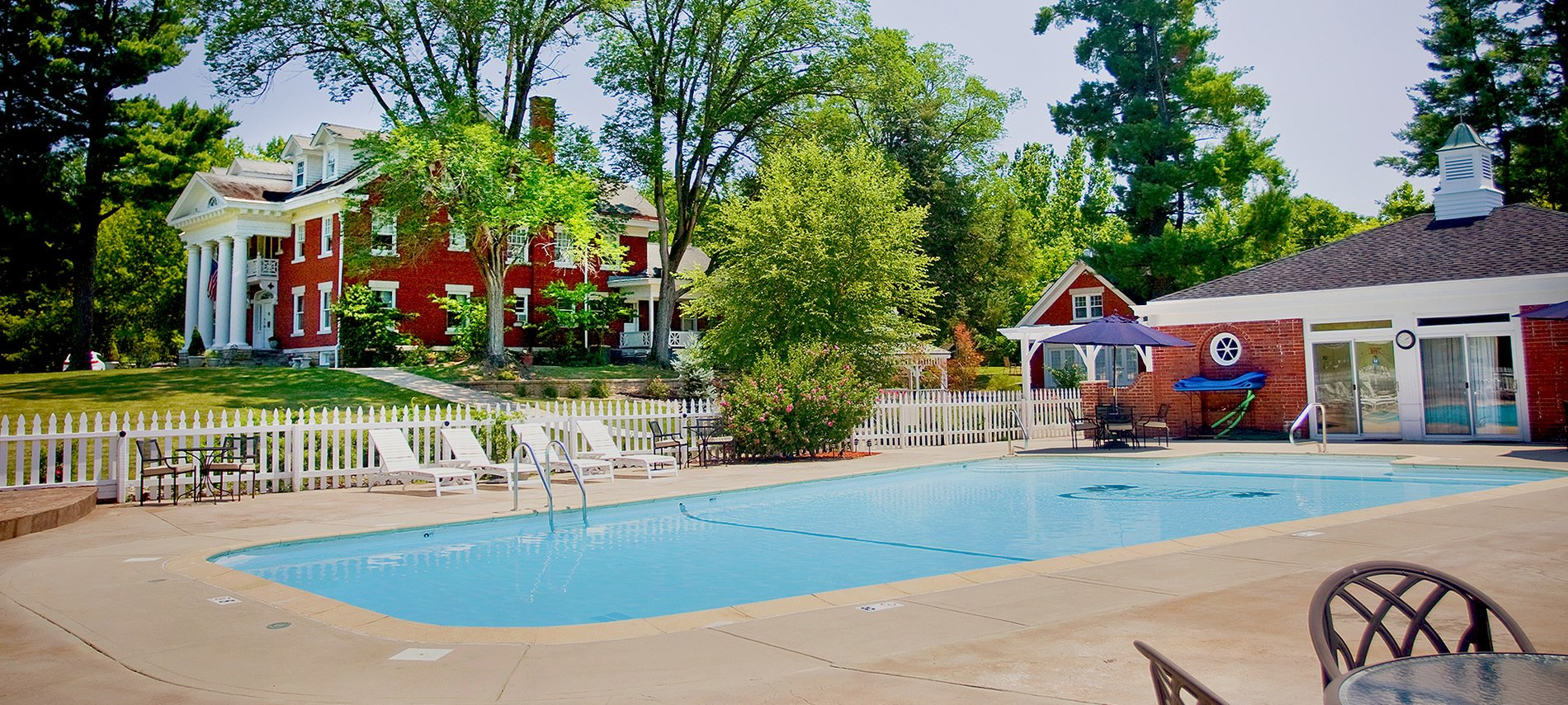 A crystal blue swimming pool in the foreground with a red brick mansion in the background