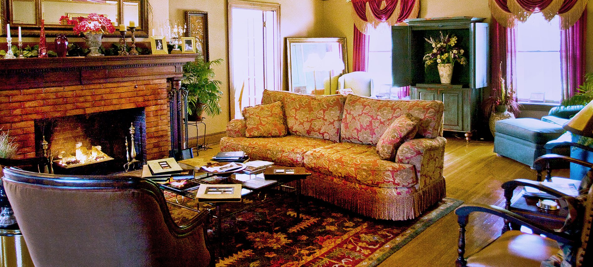 A living room with an overstuffed burnt orange sofa to the right and a brown brick fireplace to the left