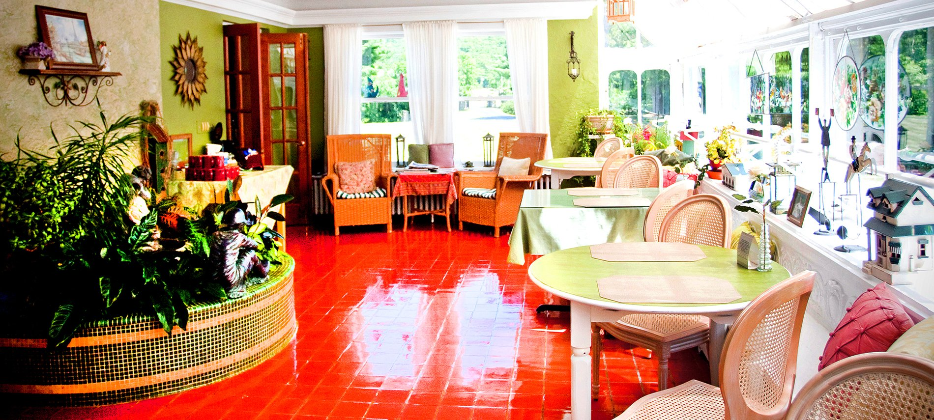 A brightly lit sunroom with red slate floor and two green tables to the right