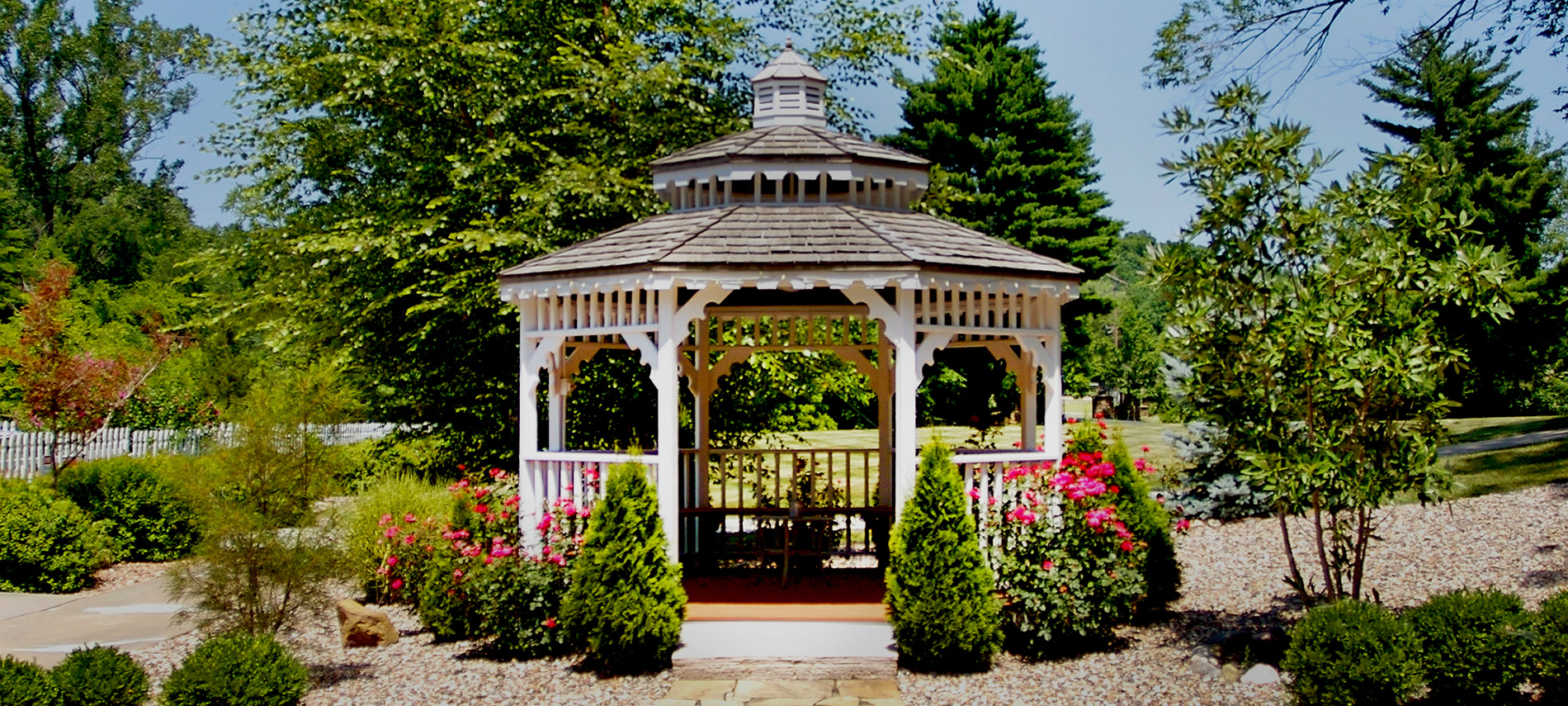 A white wood gazebo surrounded by a rock garden, shrubs and rose bushes