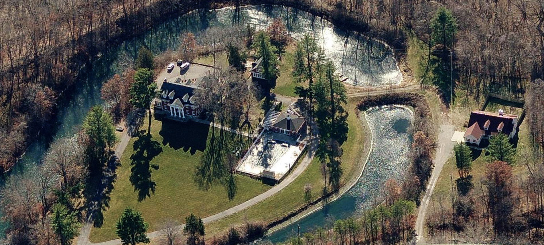 Aerial view with water surrounding a red brick mansion and pool, with a white house in a clearing to the right