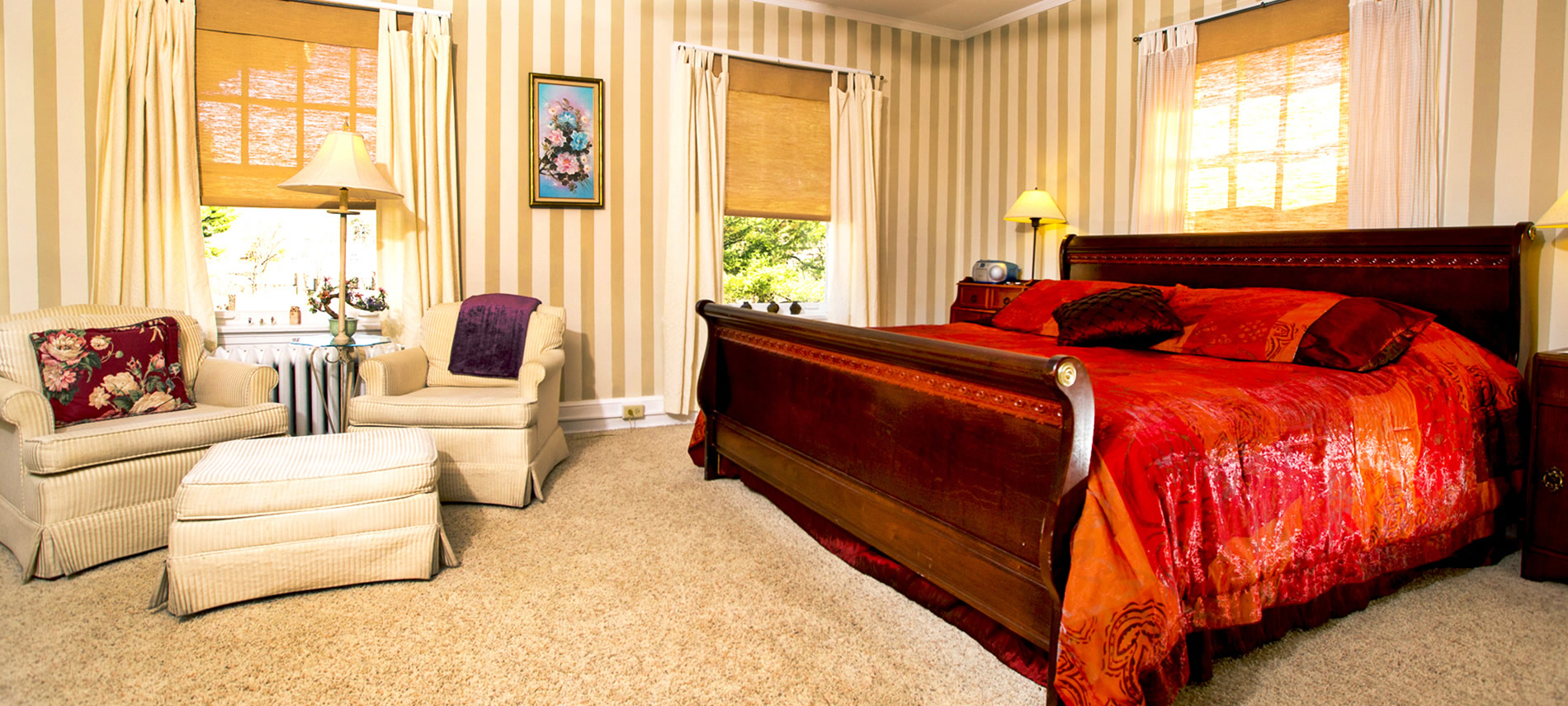 A cherry sleigh bed covered with a deep red bedspread and two cream club chairs and an ottoman