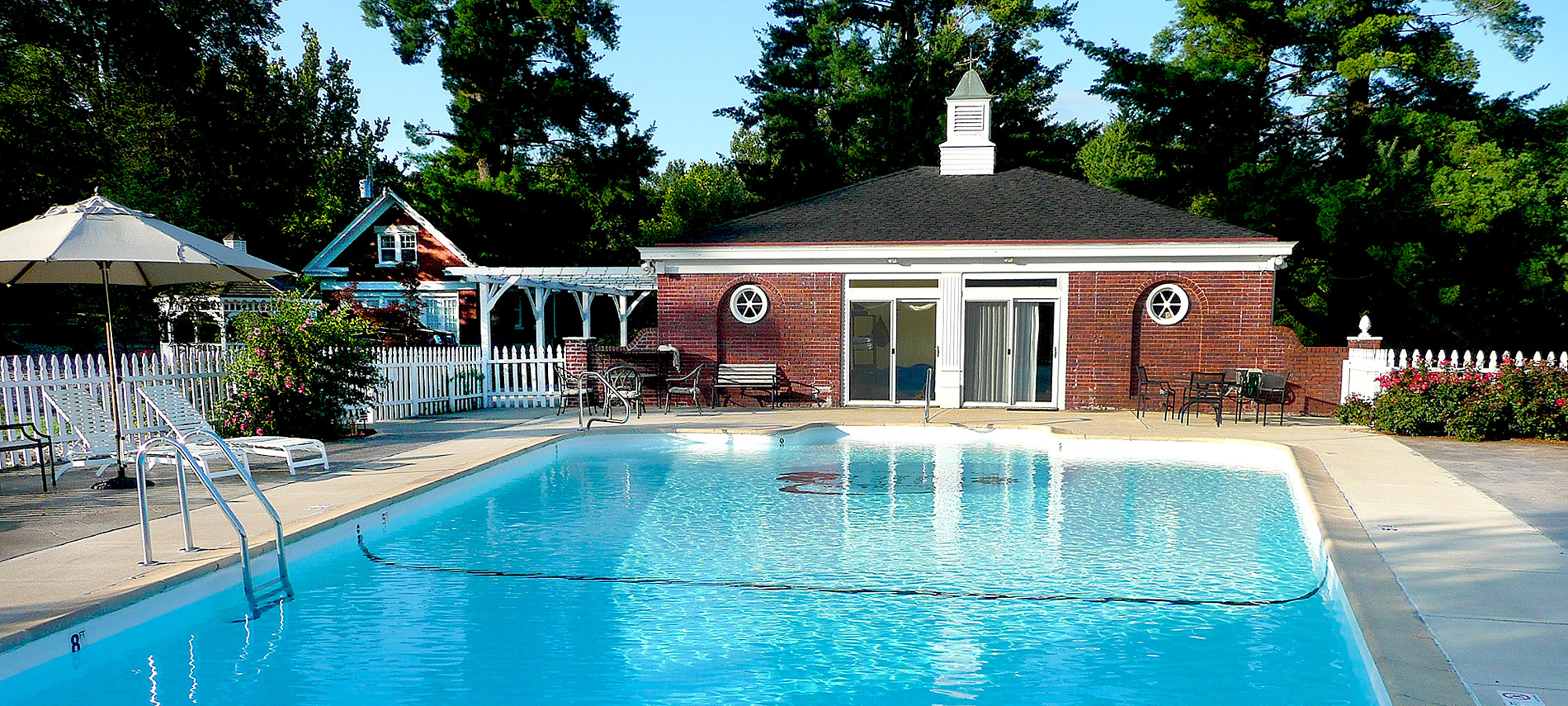 A swimming pool with red brick pool house in the background