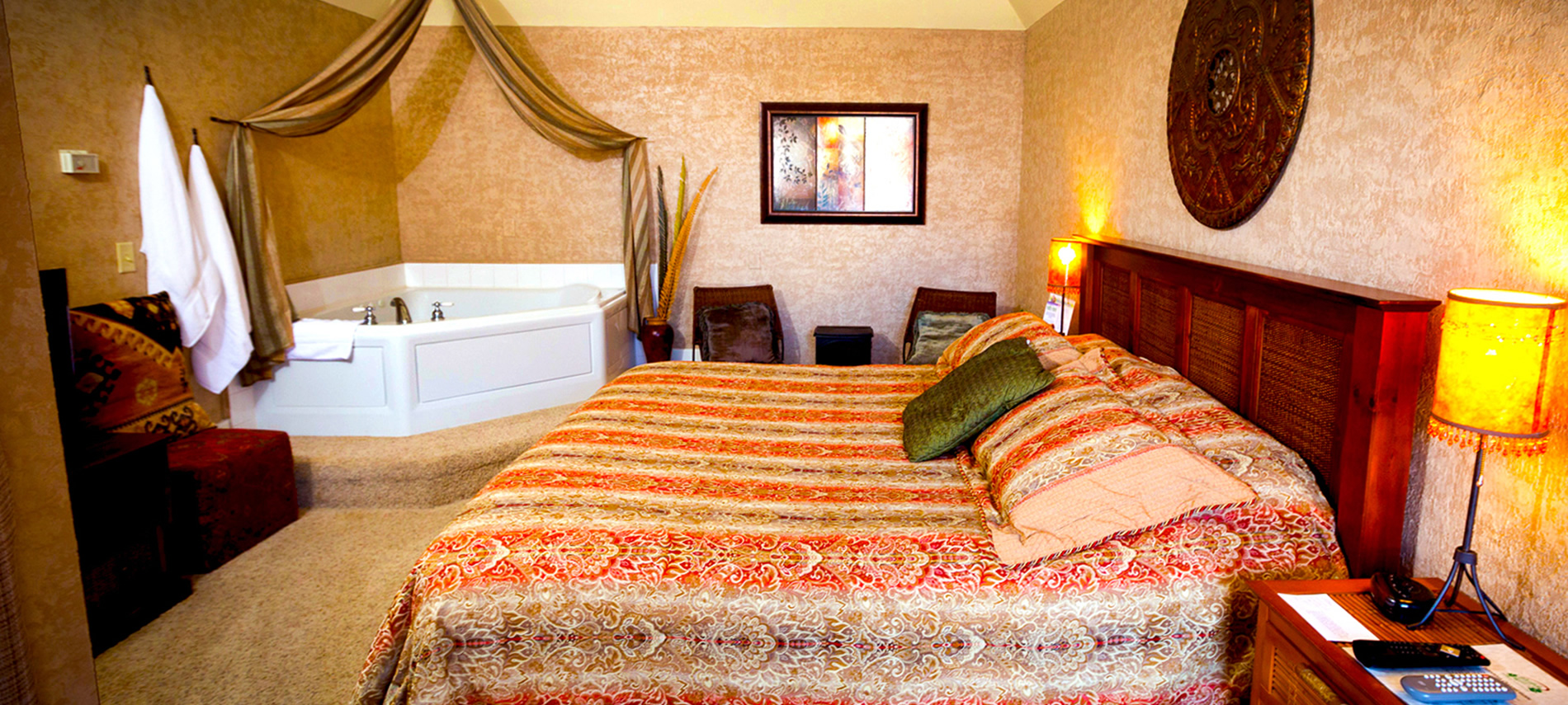 An orange and tan covered bed in the foreground with a white jacuzzi tub in the left corner background