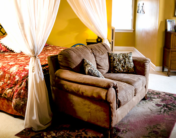 A brown cloth-covered loveseat in front of a canopy bed with orange and cream bedspread