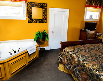 A cherry sleigh bed covered with a black and gold bedspread and gold dust ruffle on the right and a corner jacuzzi tub to the left