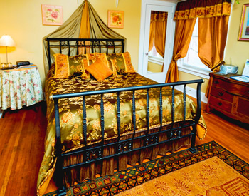 An iron sleigh bed covered with a green and gold flowered bedspread