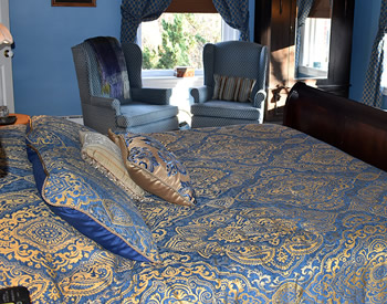 A blue and gold patterned bedspread on a wood framed bed with two blue wingback chairs and a wooden armoire in the background