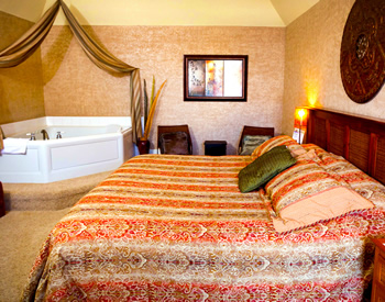 Orange and tan striped bed with a jacuzzi in the left corner of the room