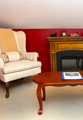 A white wingback chair and coffee table in front of an electric fireplace