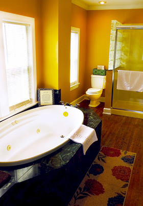 A white oval jacuzzi tub set in green marble tile inn front of two windows with a commode and shower in the background
