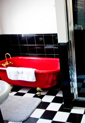 A red clawfoot tub on black and white tiled floor in front of a black tiled wall