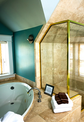 A walk-in shower framed in gold metal to the right with an oval jacuzzi tub to the left