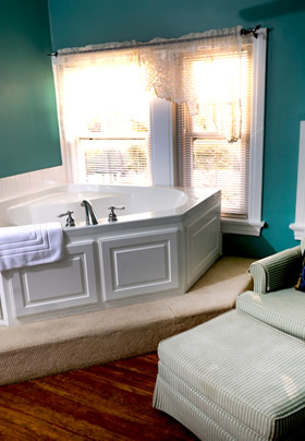 A corner jacuzzi tub in front of two windows with a green and white striped ottoman and chair