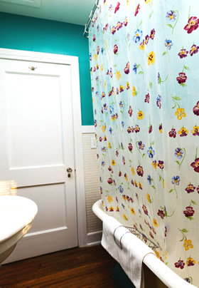 A clawfoot tub with a floral-patterned shower curtain and a white door