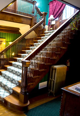 A grand wooden staircase from the side, with white and green patterned carpeting on the stairs