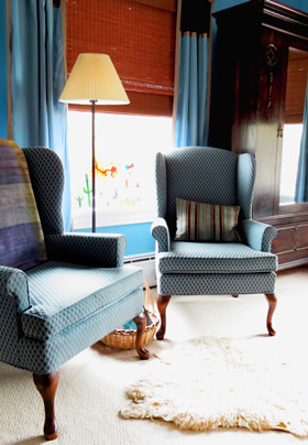 Two blue wingback chairs in front of a window with a tall lamp standing between