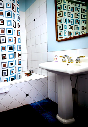 A white pedestal sink to the right with a white tiled jacuzzi tub to the left with a blue, brown and black pattered shower curtain