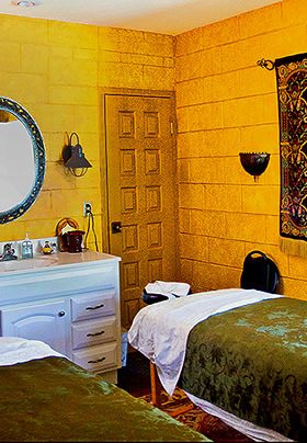 Two massage tables covered with green blankets and white sheets with a white bathroom vanity
