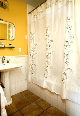 A white pedestal sink to the left with a white tiled shower to the right with a flower embroidered white curtain drawn across it