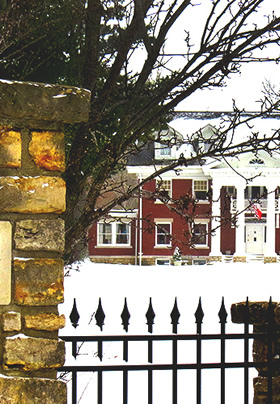 Winter scene looking through a black iron fence toward a snow-covered red brick mansion