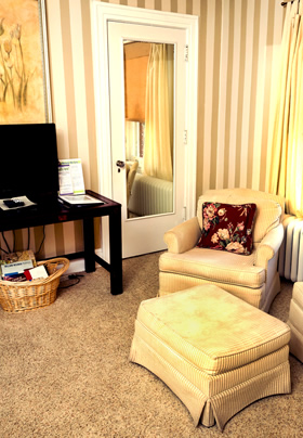 A cream colored club chair and ottoman in front cream and tan striped walls, a mirror mounted on a door in the background