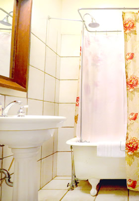 A white pedestal sink to the left with a white clawfoot tub and shower to the right