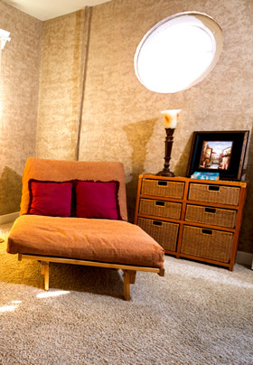 An orange futon with two deep red pillows next to a set of drawers made of a wooden frame and wicker drawers