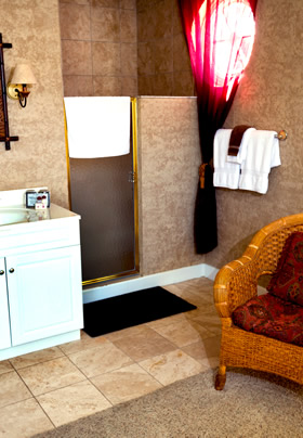 Door to a walk-in shower with a wicker chair to the right and a bathroom vanity to the left